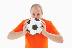 Nervous football fan holding ball Royalty Free Stock Photos