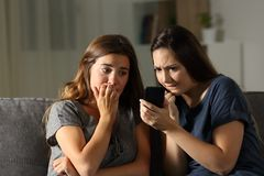 Nervous friends waiting online news in a smart phone. Sitting on a couch in the living room at home Royalty Free Stock Photos