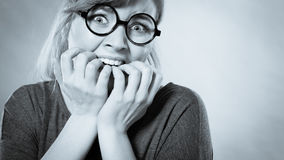 Nervous girl biting nails. Frustration mental disorder psychology fear stress concept. Nervous nerdy girl with black glasses biting nails. Stressed young blonde Stock Photo