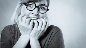 Nervous girl biting nails. Frustration mental disorder psychology fear stress concept. Nervous nerdy girl with black glasses biting nails. Stressed young blonde stock photo