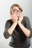 Nervous girl biting nails. Frustration mental disorder psychology fear stress concept. Nervous nerdy girl with black glasses biting nails. Stressed young blonde Stock Images