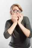 Nervous girl biting nails. Frustration mental disorder psychology fear stress concept. Nervous nerdy girl with black glasses biting nails. Stressed young blonde stock images