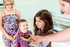 Nervous Girl Holds Snake. A visibly nervous young girl holds a snake with her siblings looking on with fascination on their faces royalty free stock photography
