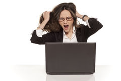 Pulls her hair and screaming. Nervous girl on a laptop pulls her hair and screaming on white background royalty free stock photos