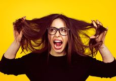 Nervous girl pulling out hair. Young brunette in eyeglasses screaming with anger and pulling out hair on orange backdrop stock photos