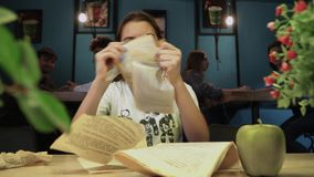 Nervous girl read the book, and then suddenly got angry and tore the book apart and left the coffee house. Young nervous girl read the book, and then suddenly stock video footage