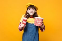 Nervous girl teenager in french beret biting lips, holding plastic cup of cola or soda, bucket of popcorn isolated on. Yellow background. People sincere royalty free stock photography