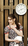 Nervous girl with toilet paper. A view of a nervous and anxious young woman standing by a wooden fence under a white clock, holding a large roll of toilet paper royalty free stock images