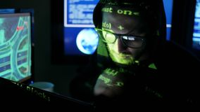 Nervous hacker working on computer, Criminal hacker cracking system, while green code characters reflect on face in dark stock video
