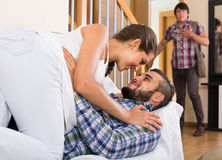 Nervous husband watching flirting spouse. Jealous husband watching spouse flirting with friend at home royalty free stock images