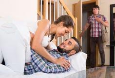 Nervous husband watching flirting spouse Stock Image