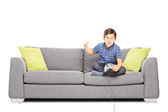 Nervous kid sitting on sofa and playing video games Stock Photography