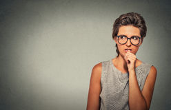 Nervous looking woman biting her fingernails craving something anxious Royalty Free Stock Photography
