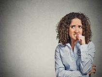 Nervous looking woman biting her fingernails craving something Royalty Free Stock Photo
