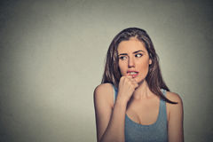 Nervous looking young woman biting her fingernails. Closeup portrait nervous looking young woman biting her fingernails craving something anxious isolated grey royalty free stock photos
