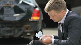 Nervous male driver counting dollars on smashed auto background, car accident. Stock footage stock footage