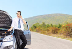 Nervous male standing next to his broken car and talking on a ph Stock Photo