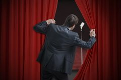 Nervous man is afraid of public speech and is hiding behind curtain.  Royalty Free Stock Photos