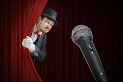 Nervous man is afraid of public speech and is hiding behind curtain.  royalty free stock image