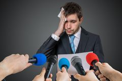 Nervous man is afraid of public speech and sweating. Many microphones in front.  stock photos