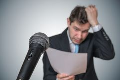 Nervous man is afraid of public speech and sweating. Microphone in front.  royalty free stock photos