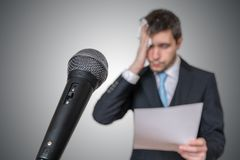 Nervous man is afraid of public speech and sweating. Microphone in front Stock Photos
