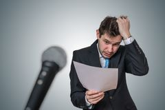 Nervous man is afraid of public speech and sweating. Microphone in front.  royalty free stock photo