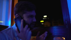 Nervous man aggressively talking phone, quarrelling with girlfriend at evening. Stock footage stock footage