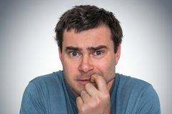 Nervous man biting his nails - nervous breakdown. Concept stock photos