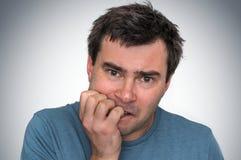 Nervous man biting his nails - nervous breakdown. Concept stock photo