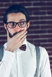 Nervous man covering mouth. Against brick wall Royalty Free Stock Image