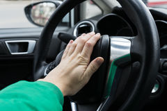 Nervous man driver pushing car horn. Close up view of hand on the steering wheel Stock Image