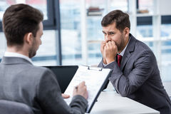 Nervous man in formal wear looking at businessman writing on clipboard during job interview royalty free stock photography