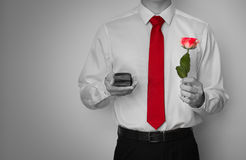 Nervous man getting ready to propose to his girlfriend. Dress shirt and red tie, holding a ring box and single red rose in black and white Royalty Free Stock Photos