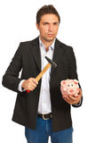 Nervous man holding hammer and piggybank royalty free stock photography