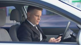 Nervous man in suit sitting on driver seat and calling on phone, late for work. Stock footage stock video