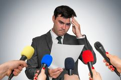 Nervous man is sweating, he afraid of public speech. Many microphones around stock images