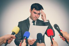 Nervous man is sweating, he afraid of public speech. Many microphones around. Retro style royalty free stock image