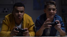 Nervous multiracial guys losing computer game, accusing each other, addiction