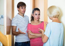 Nervous neighbors coming to old lady with complains. Upset mature women and couple of angry neighbours at doorway Royalty Free Stock Images
