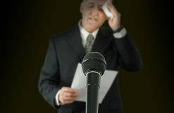 Nervous public speaker or politician wiping brow microphone in sharp focus. Microphone in sharp focus with a nervous sweaty public speaker or politician blurred royalty free stock photos