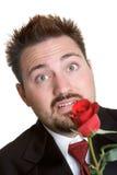 Nervous Rose Man. Nervous man giving red rose Royalty Free Stock Images
