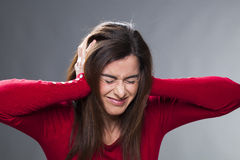 Nervous 30's brunette suffering from migraine, covering her ears with her hands Royalty Free Stock Photos