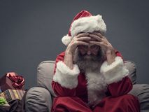 Nervous Santa Claus on Christmas eve. He is sitting on the armchair with head in hands royalty free stock images
