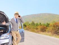 Nervous senior man on a broken car talking on a cell phone Royalty Free Stock Photos