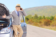Nervous senior man on a broken car talking on a phone Stock Photo