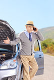 Nervous senior man on a broken car talking on a phone Stock Image