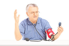 Nervous senior man measuring blood pressure with sphygmomanometer and gesturing royalty free stock photos