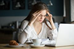 Nervous stressed female student feeling headache studying in caf. Nervous stressed women feeling anxiety or strong headache massaging temples studying in cafe Stock Image