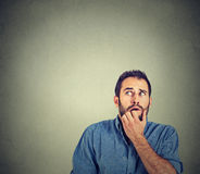 Nervous stressed young man student biting fingernails looking up. Closeup portrait nervous stressed young man student biting fingernails looking up anxiously Royalty Free Stock Image